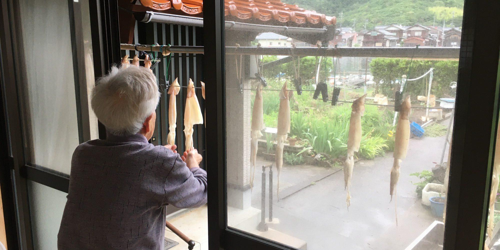 軒下にイカを干す老婦人
